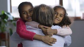 Portrait of cute granchildren embracing grandpa stock video