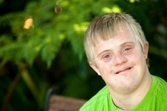 Portrait of cute handicapped boy in garden. royalty free stock image
