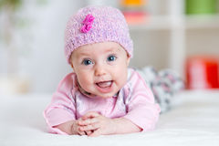 Portrait of cute happy baby girl. Portrait of adorable baby girl lying on her belly Stock Photography