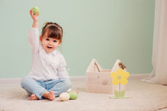 Portrait of cute happy baby girl playing with easter decorations. Close up indoor portrait of cute happy baby girl playing with easter decorations stock images