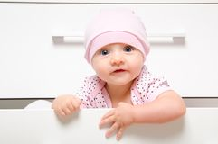 Happy baby sitting in a drawer chest. Portrait of a cute happy baby sitting in a drawer chest royalty free stock image
