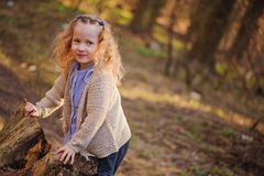 Portrait of cute happy child girl playing with tree in early spring forest Stock Photography