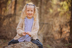 Portrait of cute happy child girl sitting on the tree in early spring forest Stock Image