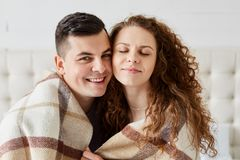Portrait of cute happy couple sitting in bed embrace each other. Beautiful girl with long curly hair sits with closed eyes with. Her husband, guy hugs his stock image