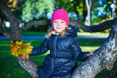 Portrait of cute happy girl sitting on tree branch in autumn par Stock Photography