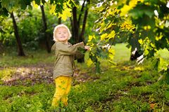Portrait of cute happy little boy having fun in summer park after rain. Active outdoors game for little children stock photo