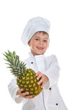 Cute happy little chef holding pineapple on white background. Stock Photography