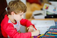 Portrait of cute happy school kid boy at home making homework. Little child writing with colorful pencils, indoors stock image