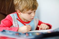 Portrait of cute happy school kid boy at home making homework. Little child writing with colorful pencils, indoors stock photography
