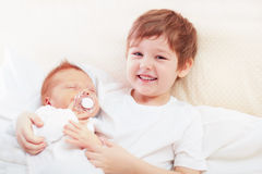 Portrait of cute happy siblings. young boy holding his infant brother Stock Image