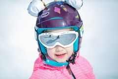 Portrait of cute happy skier girl in helmet and goggles in a winter ski resort. At winter holiday. Helmet is decorated with ears and tail like a tiger cub royalty free stock photography