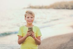Portrait of cute happy smiling white kid using modern smart phone royalty free stock photo