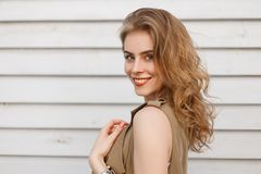 Portrait of a cute happy young woman with a beautiful smile with natural make-up with curly blond hair with blue eyes. In summer clothes posing near a wooden stock photo