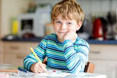 Portrait of cute healthy happy school kid boy at home making homework. Little child writing with colorful pencils stock photos