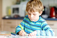 Portrait of cute healthy happy school kid boy at home making homework. Little child writing with colorful pencils royalty free stock images