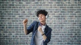 Portrait of cute hipster dancing in headphones on brick background having fun. Portrait of cute hipster attracxtive young woman dancing in headphones on brick stock video