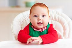 Portrait of cute infant baby boy in elf costume sitting in highchair Stock Photo