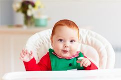 Portrait of cute infant baby boy in elf costume sitting in highchair Stock Image