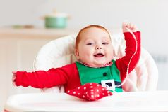 Cute infant redhead baby boy in elf costume playing with red star in highchair. Portrait of cute infant redhead baby boy in elf costume playing with red star in Royalty Free Stock Image