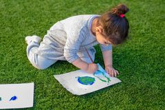 Portrait of the cute kid drawnig a picture of earth globe. stock photos