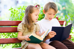Portrait of cute kids reading book Stock Photography