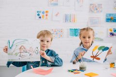 Portrait of cute kids showing drawings in hands at table. In classroom royalty free stock images