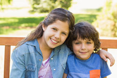 Portrait of cute kids sitting on park bench Stock Photography