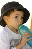 Portrait cute latino boy drinking water. A cute and happy looking latino boy is drinking water out of coloured bottle Royalty Free Stock Photo