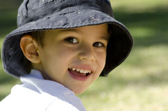 Portrait cute latino child. An adorable latino boy of three years is happily smiling for the camera, with blurred outdoor background Royalty Free Stock Photography