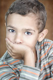 Portrait of cute litle boy covering his mouth. Closeup portrait of a 5 year old child looking at the camera and covering his mouth Royalty Free Stock Photography