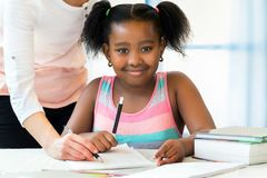 Portrait of cute little african student doing homework with cauc. Close up portrait of cute little african student doing homework with caucasian teacher Royalty Free Stock Image