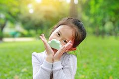 Portrait of cute little Asian kid girl smelling some food in her hands at summer park.  stock photos