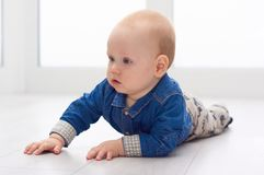 Little baby play on the floor. Portrait of a cute little baby in blue denim shirt laying on the floor. Candid image of young baby playing at home stock photography