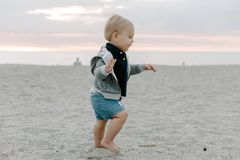Portrait of Cute Little Baby Boy Child Playing and Exploring in the Sand at the Beach During Sunset Outside on Vacation in Hoodie royalty free stock photography
