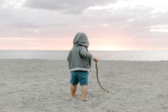 Portrait of Cute Little Baby Boy Child Playing and Exploring in the Sand at the Beach During Sunset Outside on Vacation in Hoodie royalty free stock photo