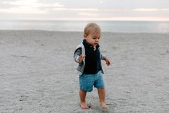 Portrait of Cute Little Baby Boy Child Playing and Exploring in the Sand at the Beach During Sunset Outside on Vacation in Hoodie stock image