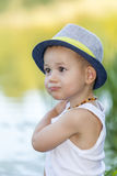 Portrait of a cute little baby boy with a hat. Portrait of a cute little boy with a hat, stands by the river and enjoy the beautiful and sunny day. Baby boy Royalty Free Stock Images