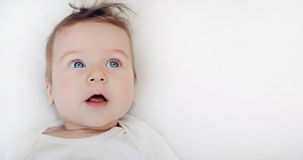 Portrait of cute little baby boy lying on soft white pillow Royalty Free Stock Images