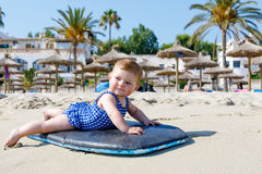 Portrait of cute little baby girl in swim suit on beach in summer. Royalty Free Stock Images
