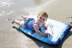 Portrait of cute little baby girl in swim suit on beach in summer. Adorable child having fun on surf board. Baby fashion for swimsuit Stock Images