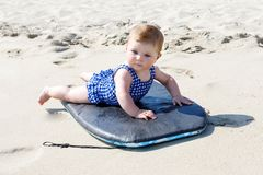Portrait of cute little baby girl in swim suit on beach in summer. Adorable child having fun on surf board. Baby fashion for swimsuit Royalty Free Stock Images