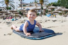 Portrait of cute little baby girl in swim suit on beach in summer. Adorable child having fun on surf board. Baby fashion for swimsuit Stock Image