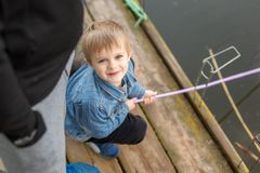 Portrait of cute little blond boy sitting on wooden pier near father. Adorable child having fun and smiling at lake or river shore royalty free stock image