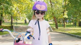 Little cute girl with bike in park stock video