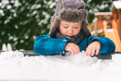 Portrait of a cute little boy. Adorable kid boy playing in sandbox full of snow, wearing warm hat Stock Photography