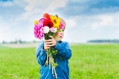 Portrait of a cute little boy. Beautiful bouquet of bright and colorful flowers holding by cute toddler boy Stock Images