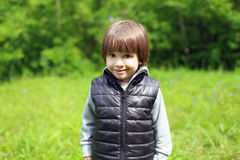 Portrait of cute little boy in black waistcoat outdoors Stock Photos