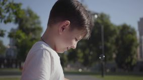 Portrait of cute little boy blowing soap bubbles. Cute child spending time alone outdoors. Summertime leisure. Adorable. Kid has fun in the park stock video footage