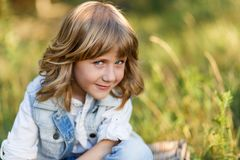 A portrait of a cute little boy with blue eyes and long blond hair sitting on a basket outside at sunset royalty free stock photography