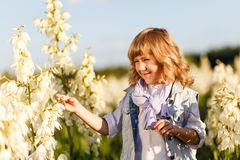 A portrait of a cute little boy with blue eyes and long blond hair outside in the field of flowers having fun stock photos
